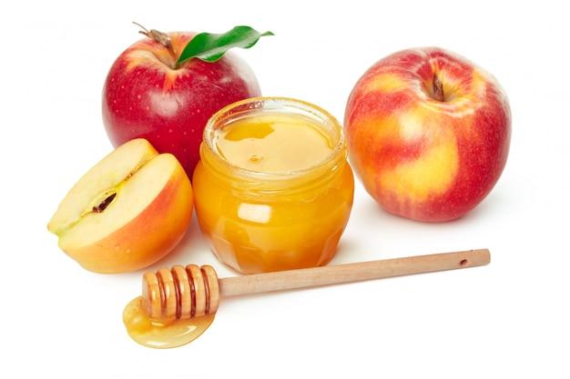 Яблоки и банку меда для еврейского новогоднего праздника изолированы Premium Фотографии