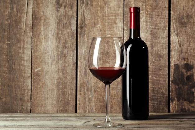 ガラスとテーブルの上のおいしい赤ワインの瓶 Premium写真