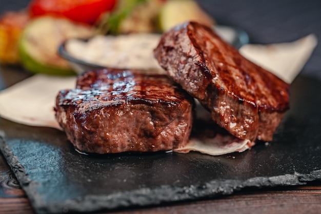 灰色のスレートに野菜と牛肉のグリルステーキ Premium写真