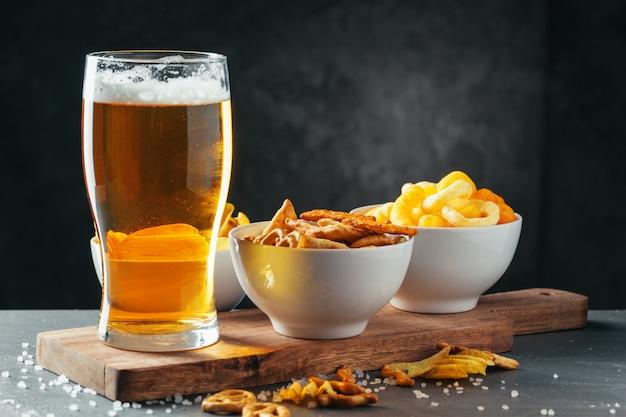 暗い石のスナックボウルとラガービールのグラス Premium写真