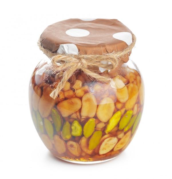 分離された甘い蜂蜜とガラスの瓶 Premium写真