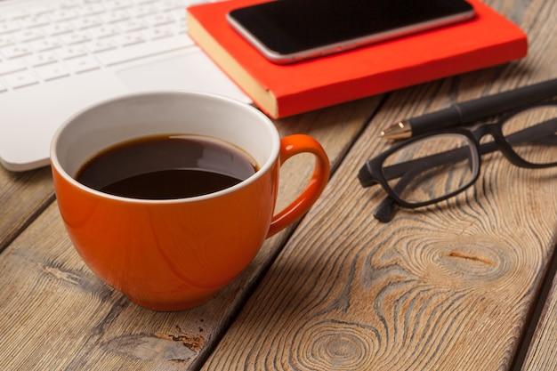 木製テーブルの上のオレンジ色のプレートにコーヒーカップ。オフィスインテリア Premium写真