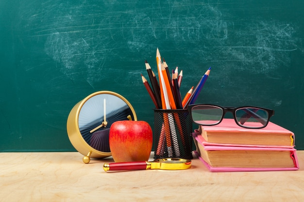 机の上の本、紙、鉛筆の山に赤いリンゴ Premium写真