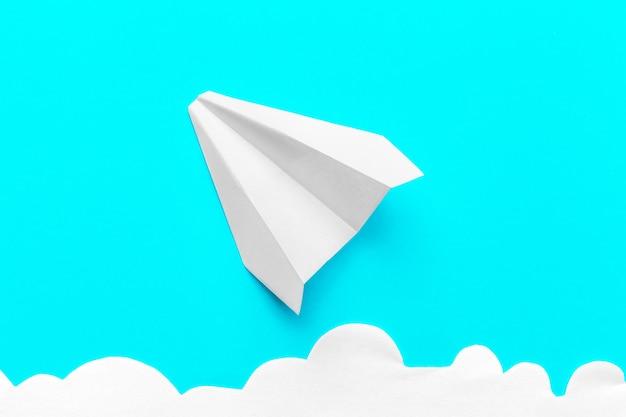 Летающий бумажный самолетик в облаках на синем фоне Premium Фотографии