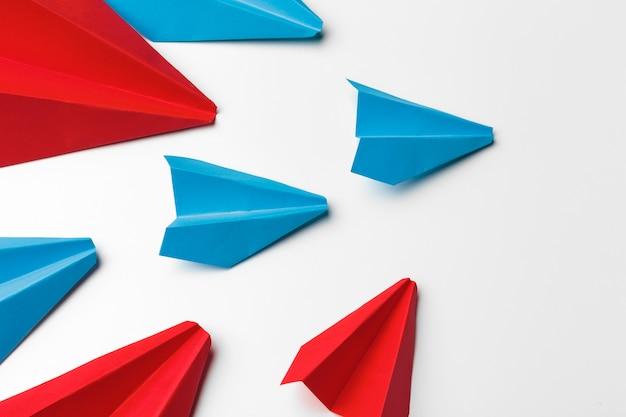 Красные и синие бумажные самолетики на белом Premium Фотографии