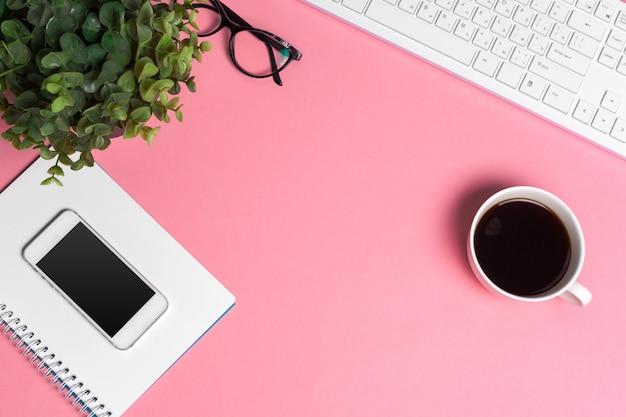 コンピューターのキーボードと用品、トップビューで女性のピンクの創造的なワークスペース Premium写真