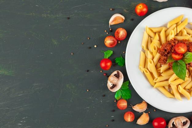 肉、トマトソース、野菜、テーブルの背景のパスタ Premium写真