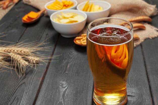 ラガービールと木製のテーブルのスナック。 Premium写真