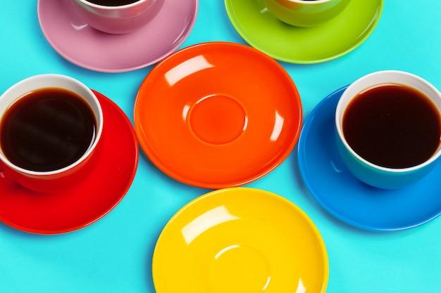 カラフルなコーヒーカップとカラフルな活気に受け皿 Premium写真