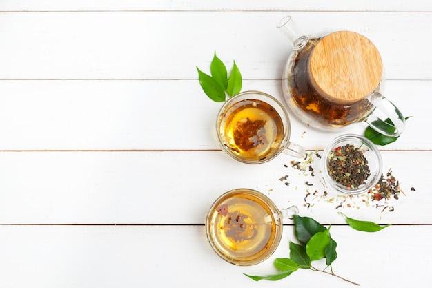 ティーポットと白い木製の背景にお茶のカップ Premium写真