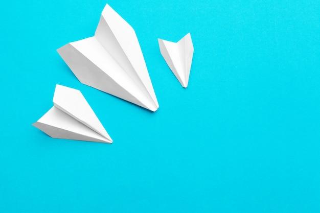 Белый бумажный самолетик на синем фоне Premium Фотографии