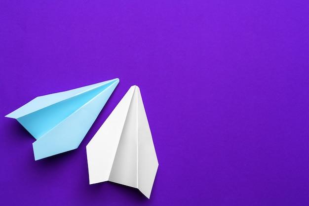Белый бумажный самолетик на фиолетовом фоне Premium Фотографии