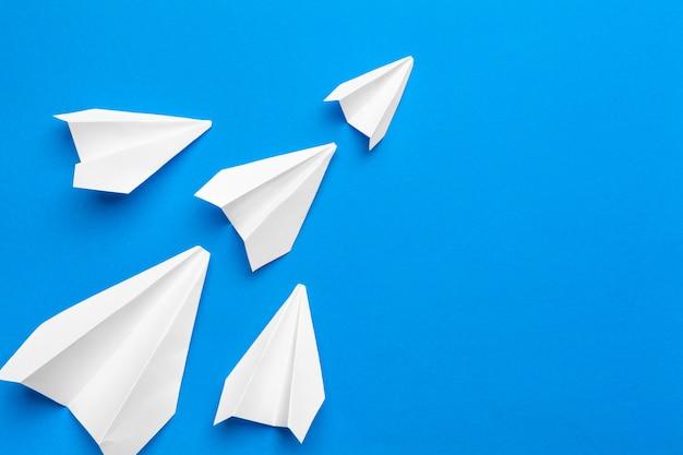 Белый бумажный самолетик на фоне бумаги военно-морского флота Premium Фотографии