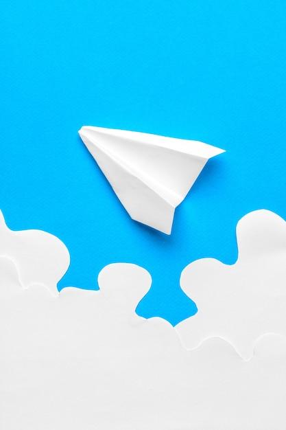 Летающий бумажный самолетик в облаках. концепция полета, путешествия Premium Фотографии