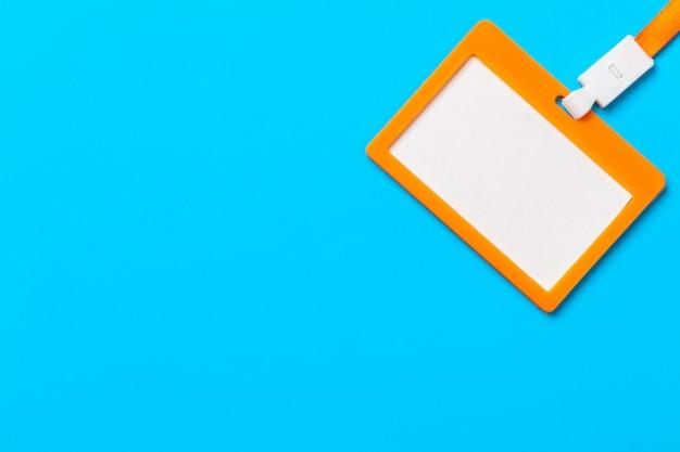 青い紙の背景にコピースペースを持つオレンジ色のバッジ Premium写真