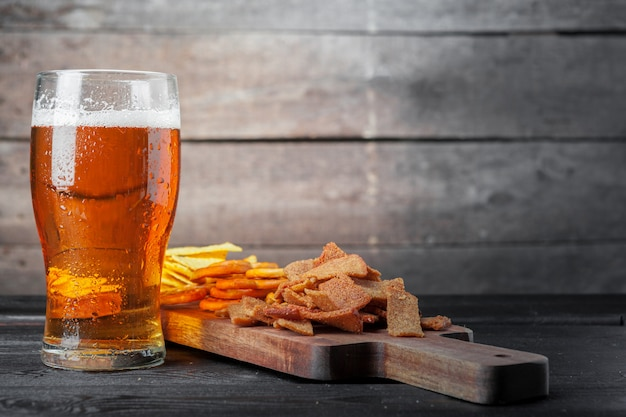 ラガービールと木製のテーブルのスナック。ナッツ、チップ、プレッツェル Premium写真