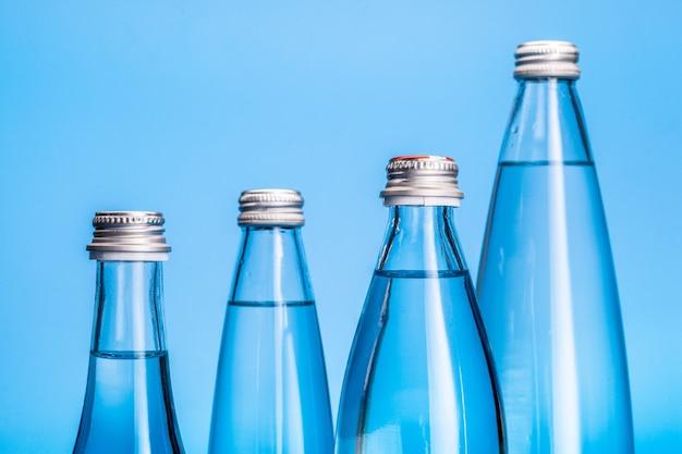 明るい青の背景にガラスの水のボトル Premium写真