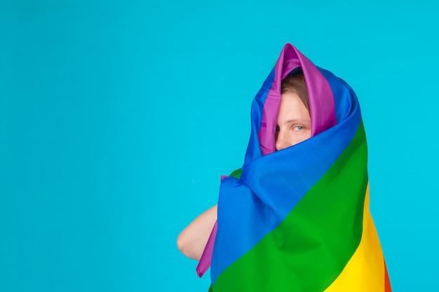 Молодая женщина покрыта флагом лгбт Premium Фотографии