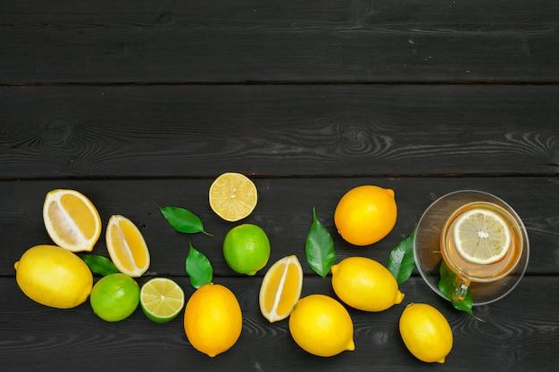 レモンティーとレモンとライムの木製テーブル Premium写真