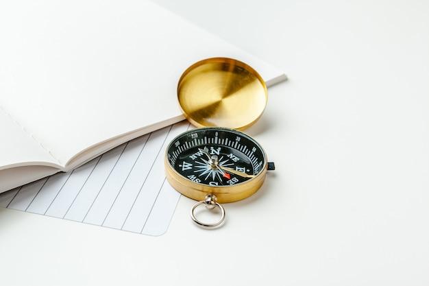航海ノートと白いテーブルの上の黄金の羅針盤の黒いメモ帳 Premium写真