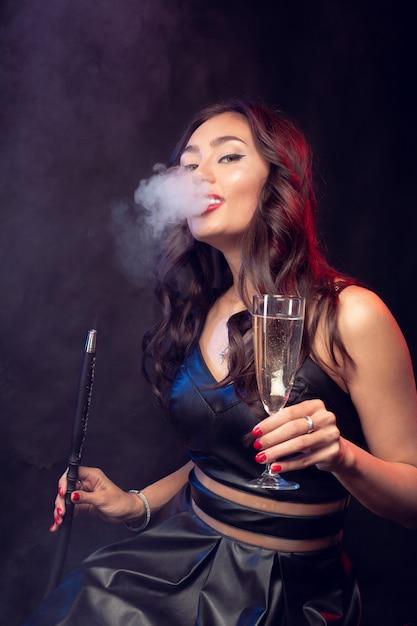 Милая женщина курит кальян и пьет коктейль в баре Premium Фотографии