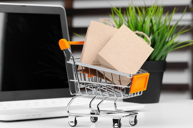ミニショッピングカートと机の上のノートパソコン Premium写真