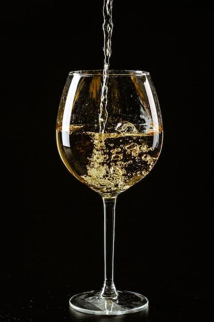 Белое вино наливают в бокал на темном фоне Premium Фотографии