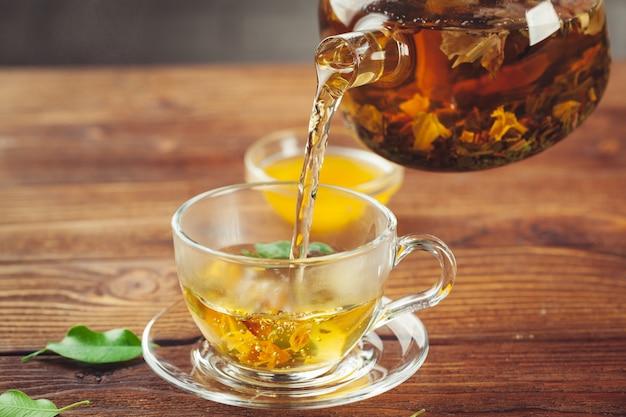 木製のテーブルに紅茶のカップとガラスのティーポット Premium写真