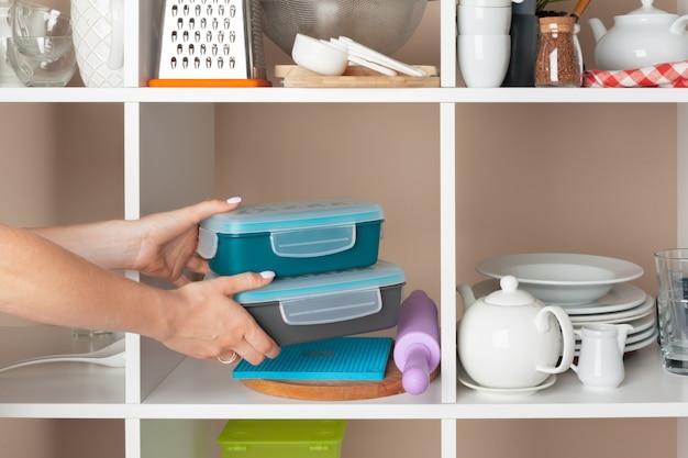台所の棚から食器の部分を取って女性手 Premium写真