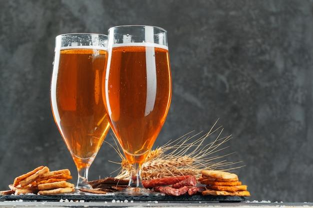 ブレッツェルと乾燥ソーセージスナックとビールのグラスをクローズアップ Premium写真
