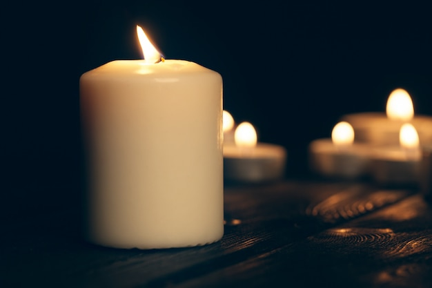 Свечи горят в темноте над черными. поминальная концепция. Premium Фотографии