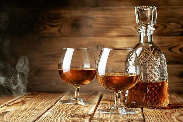 Коньяк или виски в бокалах на деревенском фоне Premium Фотографии