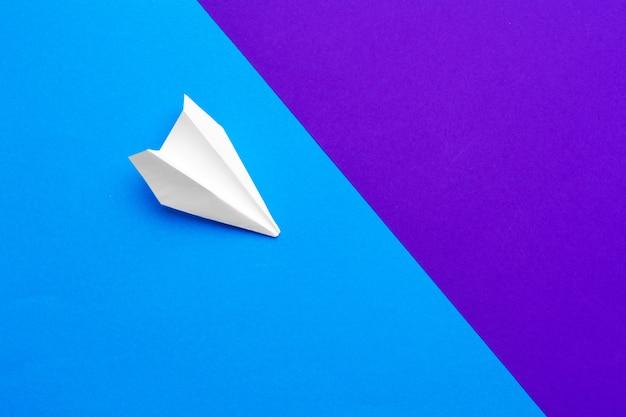 Белый бумажный самолетик на цветном блоке синий и фиолетовый Premium Фотографии