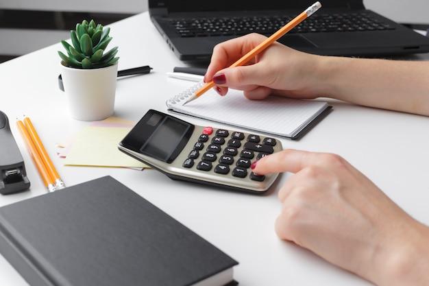 Бизнес женщина, работающая с рукой финансовых данных, используя калькулятор Premium Фотографии