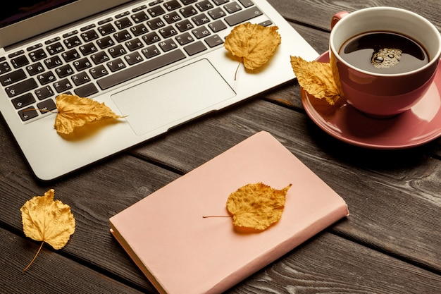 空白のノートブックとラップトップのオフィスのテーブル Premium写真