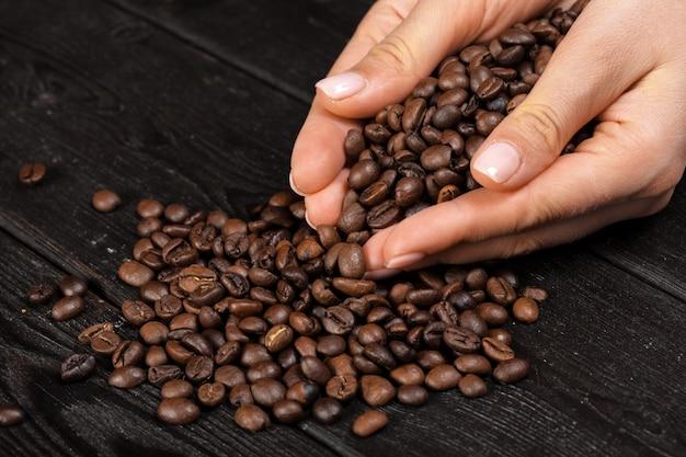 Рука кофе с кофе в зернах на деревянный стол Premium Фотографии