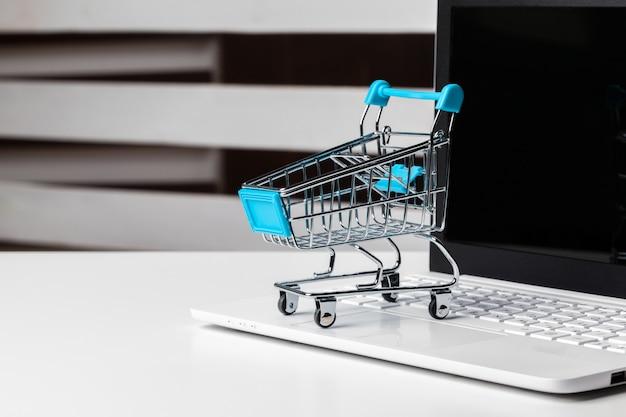 オンラインショッピングのコンセプト。テーブルの上の小さなおもちゃのトロリーとガジェット Premium写真