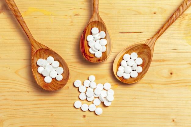 薬のカプセル、木のスプーンの丸薬 Premium写真