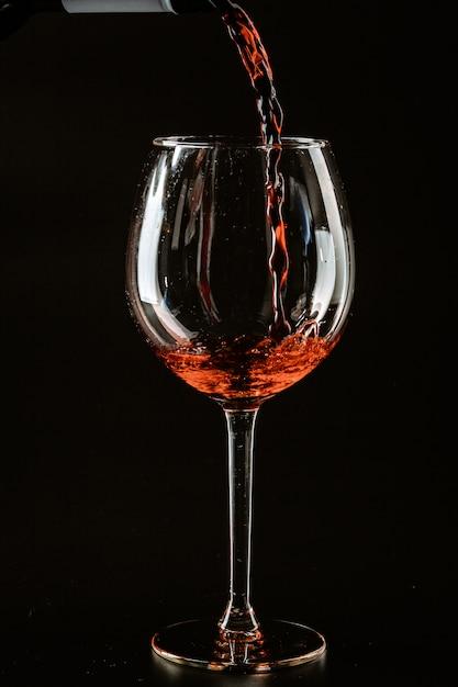 Красное вино наливают в бокал на темном Premium Фотографии