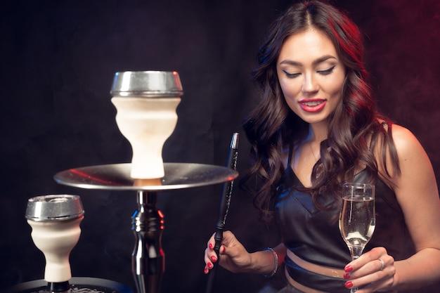 Молодая женщина курит кальян Premium Фотографии