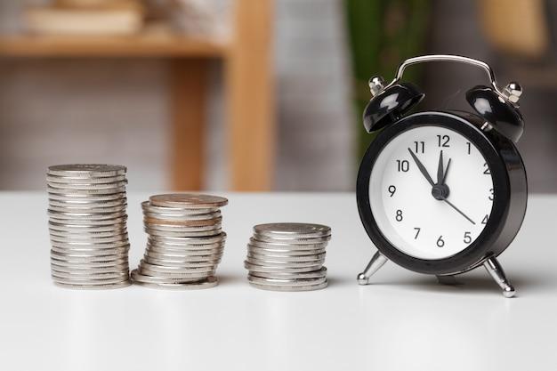 Будильник и деньги монеты на столе. Premium Фотографии