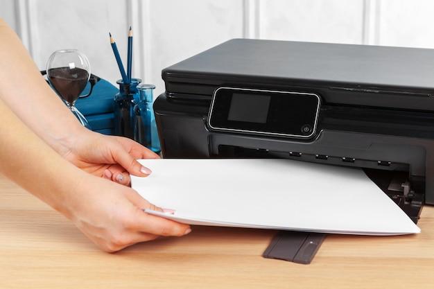 オフィスのゼロックスマシンでコピーを作る女性秘書 Premium写真