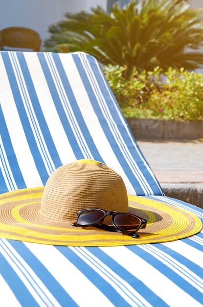 プールサイドのデッキチェアでビーチアクセサリー。 Premium写真