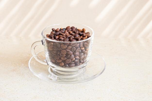 Кофейные зерна в стеклянной чашке на таблице. Бесплатные Фотографии