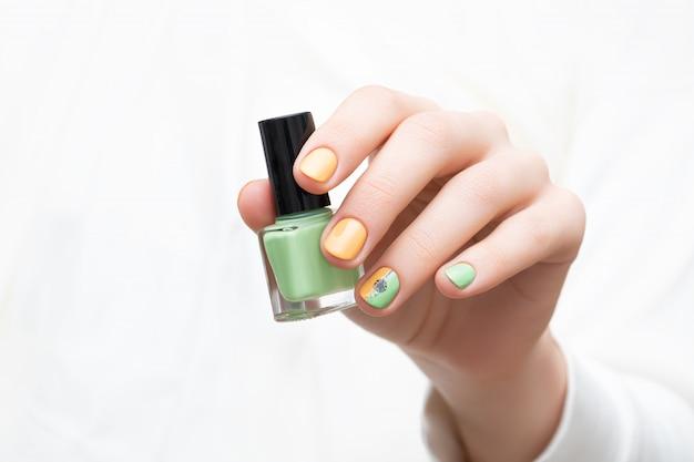 緑の爪のデザイン。タンポポのネイルアートで女性の手。 無料写真