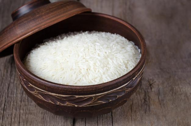 木製の背景に粘土ボウルで調理米 Premium写真