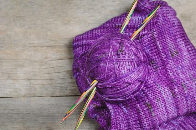 木製の背景に編み物のスレッド。編み物用アクセサリー。 Premium写真