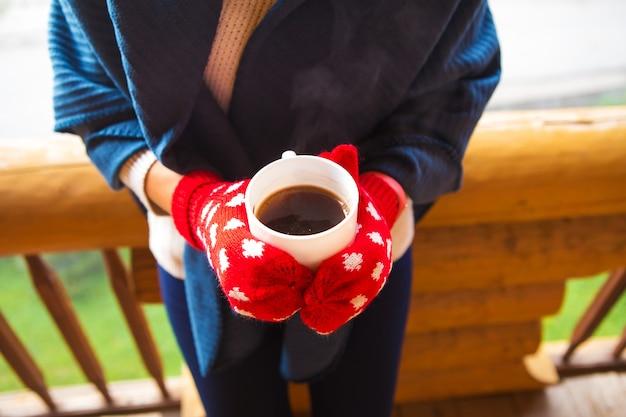 ミトンの少女はバルコニーのカルパチア山脈に立って、コーヒーを保持しています。 Premium写真