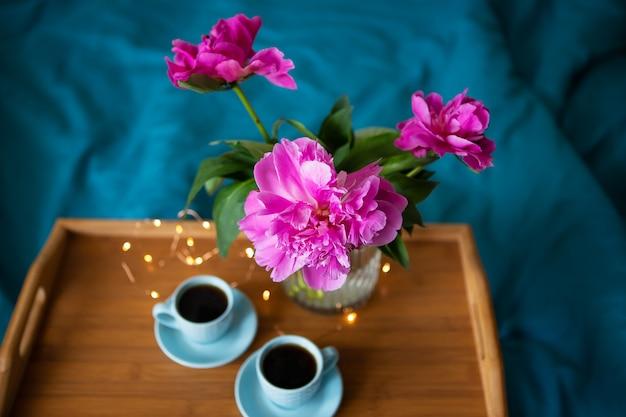 Красивые розовые пионы и две чашки кофе стоят на деревянном подносе в кровати. крупный план. вид сверху. Premium Фотографии