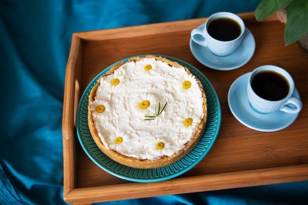 一杯のコーヒーとクリームチーズケーキは、ベッドの木製トレイの上に立っています。 Premium写真